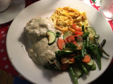 scrambled eggs with cheese, biscuit with soysaage gravy and sautéed vegetables