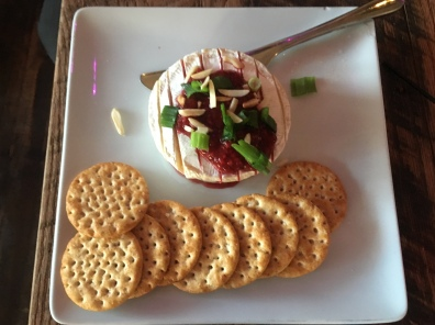 brie topped with cranberries and green onions