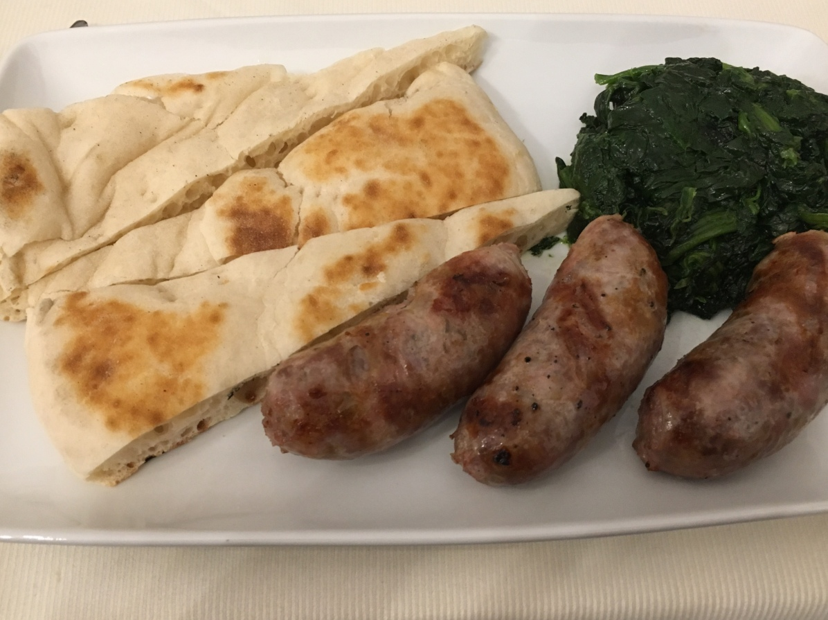 Grilled Umbrian sausages with wedges of flat bread and spinach