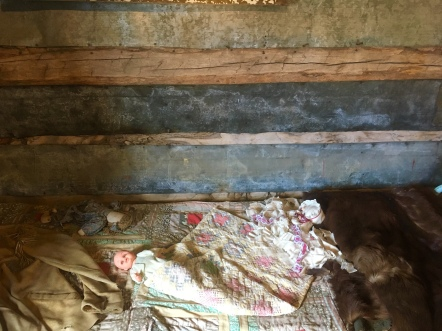bed and doll in log cabin built in 1898