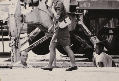 Two laborers doing excavation utility work near the sidewalk simultaneously notice the legs of a female passerby on a Grand Forks construction project in 1964.