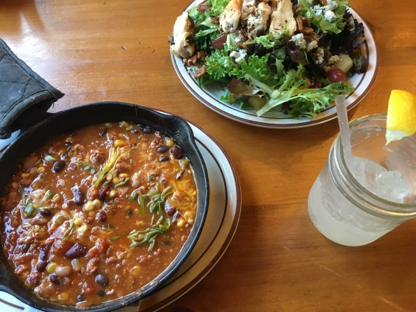 chili and corn in a cast iron skilled and chicken salad
